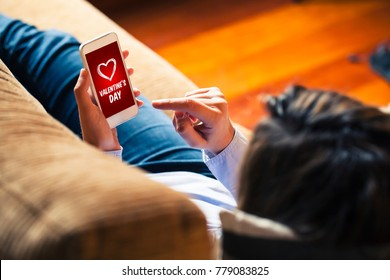 Woman holding a mobile phone with Valentine's day shopping app i