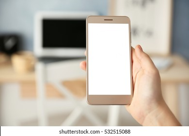 Woman holding modern cellphone at home