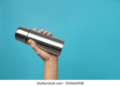 Woman holding modern thermos on light blue background, closeup. Space for text