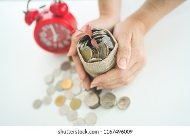 Woman holding money sack or bag on the white background with alarm clock. business, finance, retirement and money Saving for investment concept.