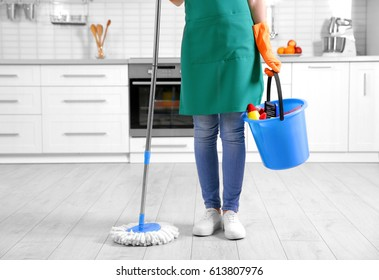 Woman holding mop and bucket with cleaning agents at home