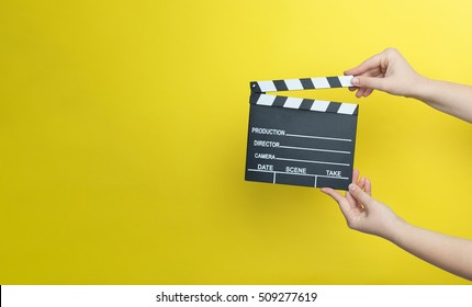woman holding movie clapper on yellow background, cinema concept