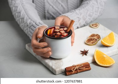 Woman holding mug with hot mulled wine on table, closeup