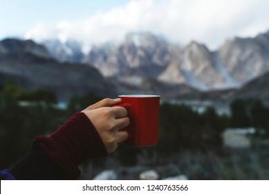 Woman holding a mug overlooking the Himalaya mountains