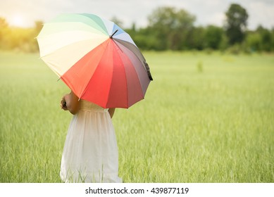 Woman holding multicolor Umbrella in meadow of thailand