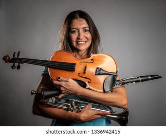 woman holding musical instruments on a gray background