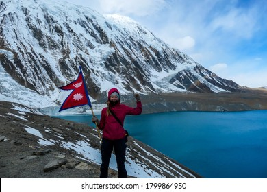 A woman holding Nepalese flag while standing at the side of turquoise colored Tilicho lake in Himalayas, Manang region in Nepal. The world's highest altitude lake. Snow capped mountains around.