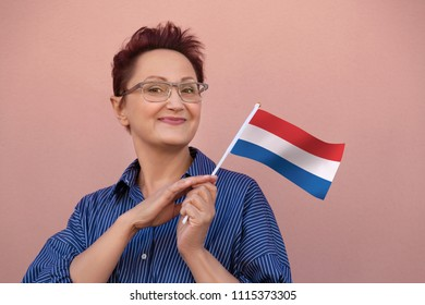 Woman holding the Netherlands Holland flag. Nice portrait of middle aged lady 40 50 years old with a national flag of the Netherlands. Visit Netherlands concept.
