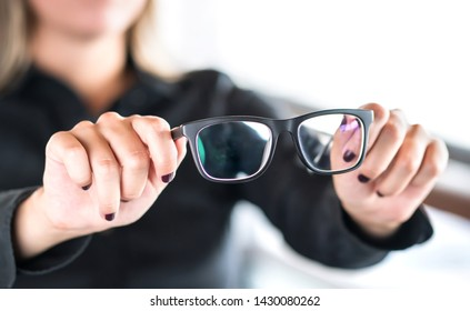Woman holding new glasses. Lenses and spectacles getting fix and repair by professional optician. Optometrist, oculist or eye doctor in clinic. Bifocal or multifocal specs. Optometry, sight and vision