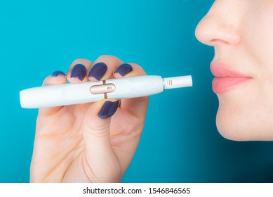 Woman is holding new heat not burn system for smoking, New trendy tobacco product technology iqos, modern hybrid cigarette device
