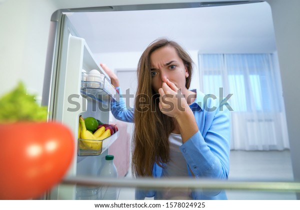 Woman holding nose due to bad unpleasant smell from spoiled food in the refrigerator