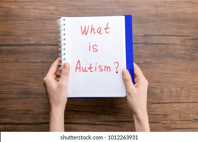"Woman holding notebook with phrase ""What is autism?"" on wooden background"