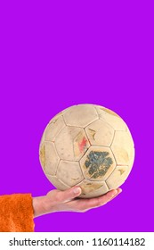 Woman holding old and weathered soccer ball in hand