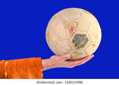 Woman holding old and weathered soccer ball in hand on a blue background