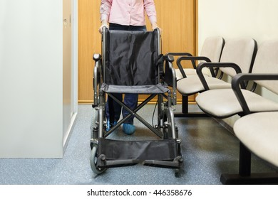 woman holding on to handle wheelchairs standing in lobby of hospital ready to transport patient