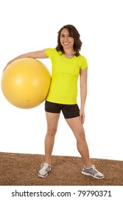 a woman holding on to her yellow workout ball with a smile on her face.