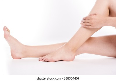 Woman holding on leg. Beautiful fit long female legs, isolated on white background. Spa woman touching her slim legs.