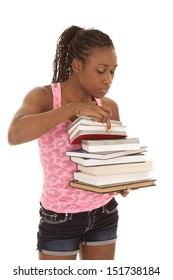 A woman holding on to a stack of books looking through them