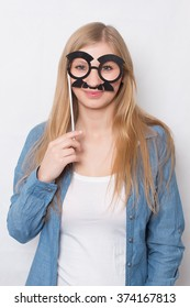 Woman holding on stick party assecoire glasses and mustache