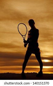 A woman holding on to a tennis racket with a beautiful sky behind her.