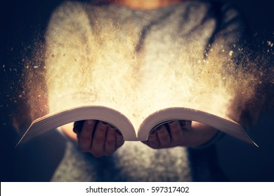 Woman holding an open book with two hands. Light coming out of the book as a concept of learning, education, knowledge and religion