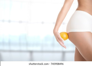 Woman holding an orange against her thighs, isolated in green