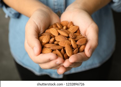 Woman holding organic almond nuts in hands, closeup