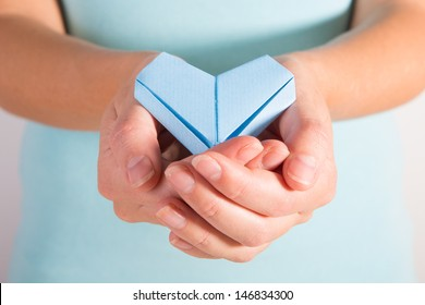A woman holding out a blue origami heart in cupped hands