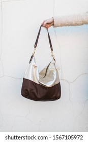 Woman holding out leather hobo purse, white background