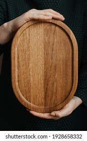 Woman holding an oval shaped wooden plate. Beautiful crockery made of real wood. Dishes made of natural materials.