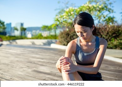 Woman holding painful ankle at park