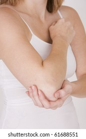 Woman holding painful elbow