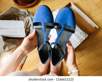 Woman holding pair of new blue elegant shoes right after unboxing - POV point of view admiring the merchandise shopping online
