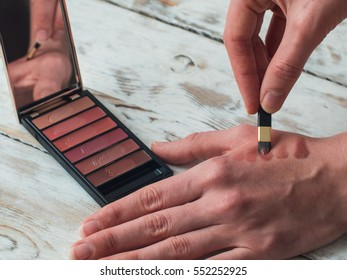 Woman holding a palette and a brush, close up