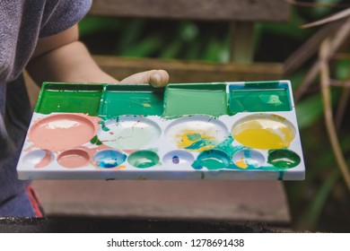 Woman holding palette of color paints with natural tree background.