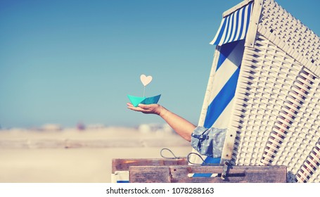 woman holding paper boat, recreation at the beach, beach chair at baltic sea