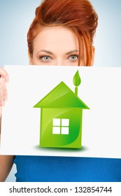 woman holding paper with illustration of green eco house