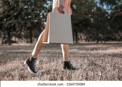 Woman holding paper kraft bag, outdoor shot in the street