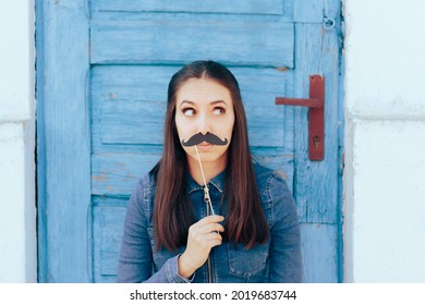 Woman Holding a Paper Mustache Looking Sideways. Young person showing bubbly personality holding party accessory
