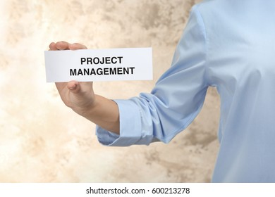 Woman holding paper sheet with text PROJECT MANAGEMENT, closeup