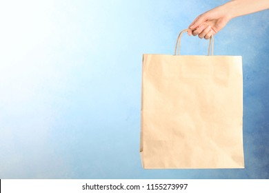 Woman holding paper shopping bag on color background