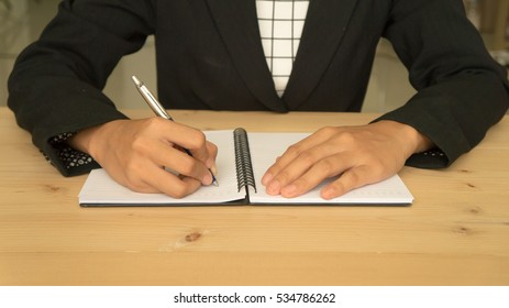 woman holding a pen and filling business plan