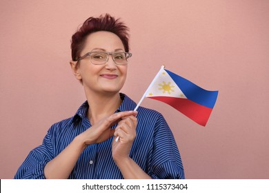 Woman holding Philippine flag. Nice portrait of middle aged lady 40 50 years old with a national flag of Philippines over pink wall background.Learning Philippine language. Visit Philippines concept.