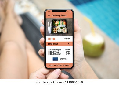 woman holding phone with app delivery sushi food on screen by the pool