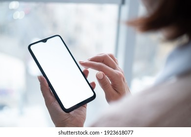 Woman holding phone with blank screen in hand on street view from window background