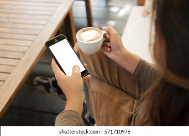 woman holding phone and coffee in cafe