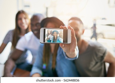 Woman holding phone with screen camera and taking selfie with three friends in light room.