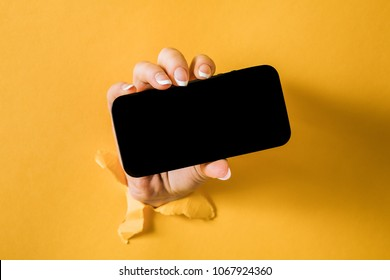 A woman holding a phone through a torn yellow paper