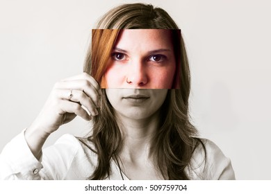 A woman holding a photo with her face in front of her face