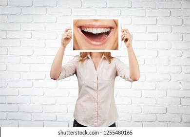 Woman holding picture with big smile. concept photo over dark background